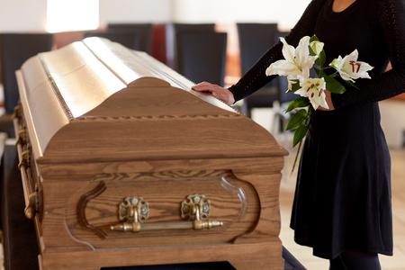 Frau mit Lilienblumen und Sarg bei Beerdigung Standard-Bild - 81084324