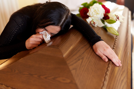 woman with coffin crying at funeral in church Фото со стока
