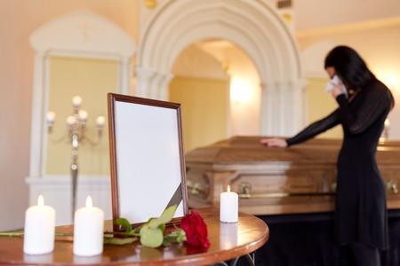 Fotolijst en vrouw die bij kist bij begrafenis huilen Stockfoto