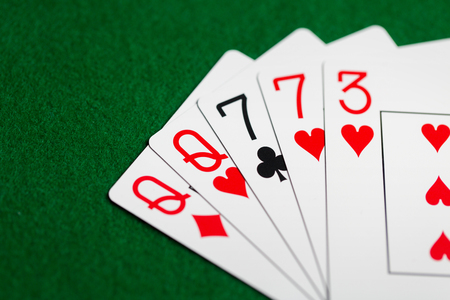 poker hand of playing cards on green casino cloth
