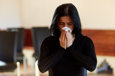 crying woman with wipe at funeral in church