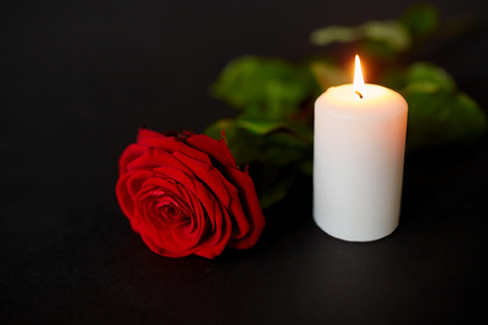 red rose and burning candle over black background Foto de archivo