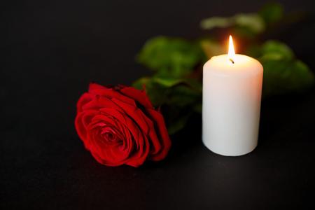 Rote Rose und brennende Kerze auf schwarzem Hintergrund Standard-Bild - 81084365