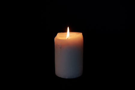candle burning in darkness over black background