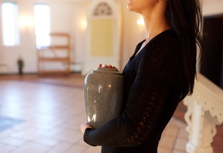close up of woman with cremation urn in church