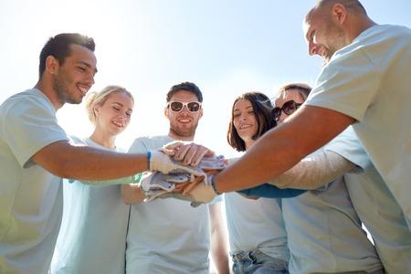 屋外の上に手を置くボランティアのグループ