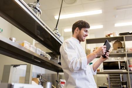 Chef kok met tablet pc in restaurant keuken Stockfoto