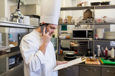 chef cook calling on smartphone at restaurant kitchen