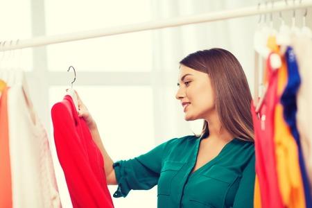 happy woman choosing clothes at home wardrobe Foto de archivo