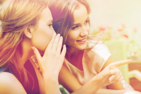 rumour: smiling young women gossiping at outdoor cafe Stock Photo