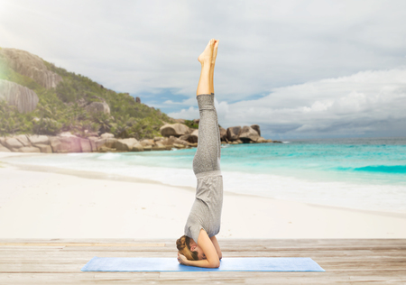 woman doing yoga in headstand pose on beach Stock Photo - 81458764