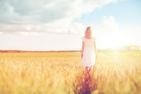 フィールド上を歩いて白いドレスの若い女性