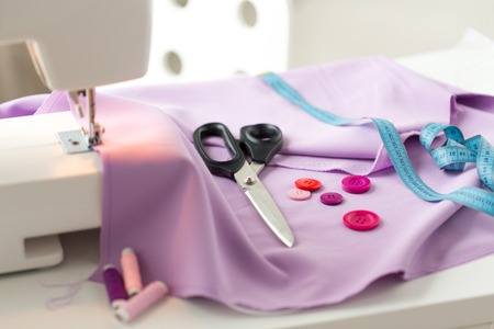 sewing machine, scissors, buttons and fabric Stock Photo