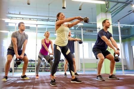 체육관에서 운동하는 kettlebells를 가진 사람들의 그룹