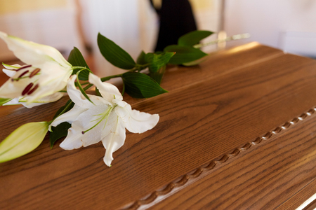 lily flower on wooden coffin at funeral in church Stock Photo