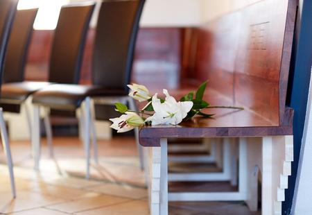 教会での葬儀でベンチに白いユリ 写真素材