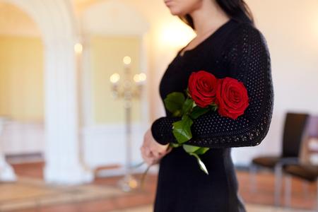 vrouw met rode rozen bij de begrafenis in de kerk Stockfoto