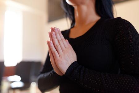 Close-up van verdrietige vrouw bidden god in de kerk