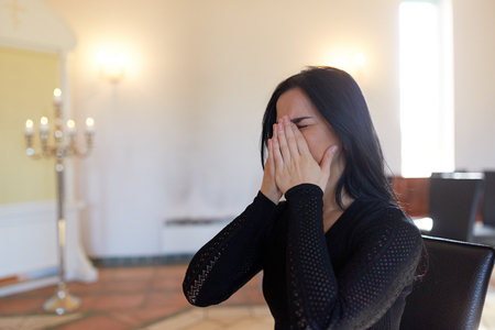 unhappy crying woman at funeral in church