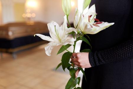 葬式でユリの花を持つ女性のクローズ アップ