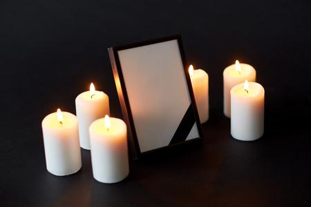 사진 프레임에 검은 리본 및 장례식에서 촛불