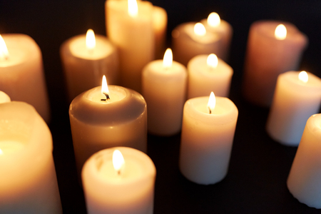 rite: candles burning in darkness over black background Stock Photo