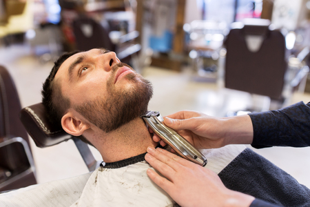 man and barber with trimmer cutting beard at salon Stock Photo