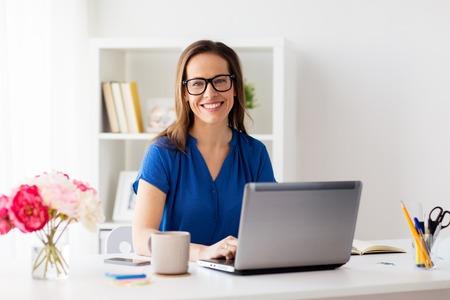 自宅のノート パソコンまたはオフィスで幸せな女 写真素材