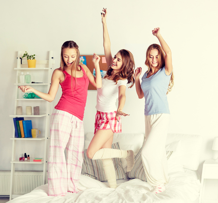 nightwear: friendship, people and pajama party concept - happy friends or teenage girls having fun and jumping on bed at home Stock Photo