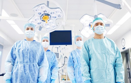 surgery, medicine and people concept - group of surgeons in operating room at hospital