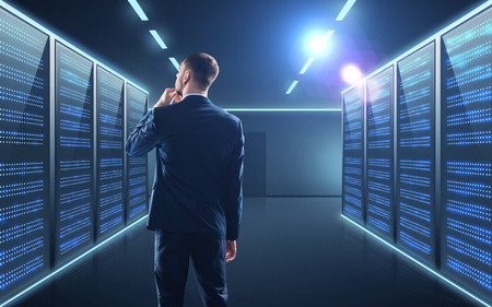 business, people and technology concept - businessman in suit over server room background