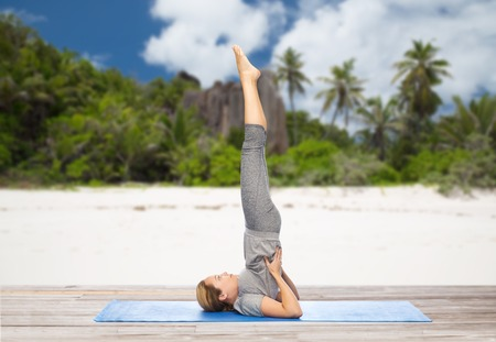 woman making yoga in shoulderstand pose on beach Stock Photo - 81598411