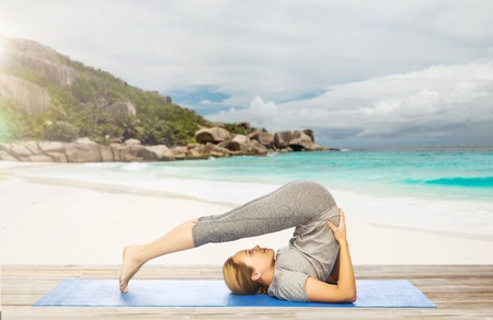 woman doing yoga in plow pose on beach Stock Photo - 81598972