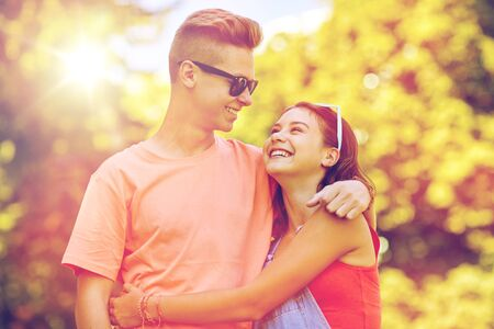 holidays, vacation, love and people concept - happy smiling teenage couple hugging and looking at each other at summer park Imagens
