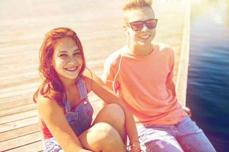 out of date: holidays, vacation, love and people concept - happy teenage couple with earphones sitting on river berth and listening to music at summer