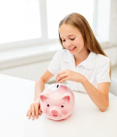 happy smiling girl putting coin into piggy bank Stock Photo