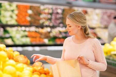 Schwangere Frau mit Tasche kaufen Orangen im Lebensmittelgeschäft Standard-Bild - 81599202