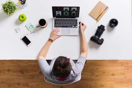 カメラのフラッシュ ドライブとのテーブルでノート パソコンを持つ女性
