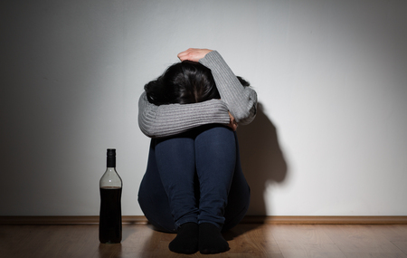 woman with bottle of alcohol crying at home