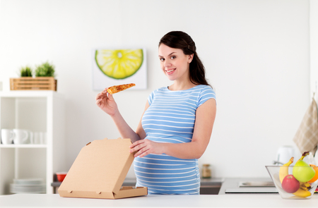 happy pregnant woman eating pizza at home kitchen Stock Photo