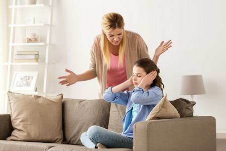 girl closing ears to not hear angry mother at home 版權商用圖片