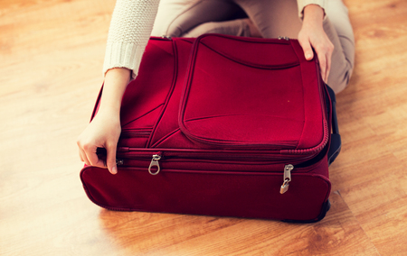 close up of woman packing travel bag for vacation Reklamní fotografie
