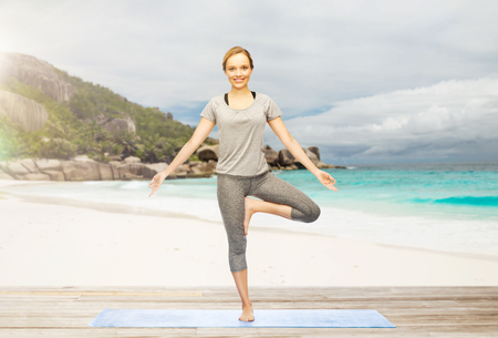 tree position: woman doing yoga in tree pose on beach Stock Photo