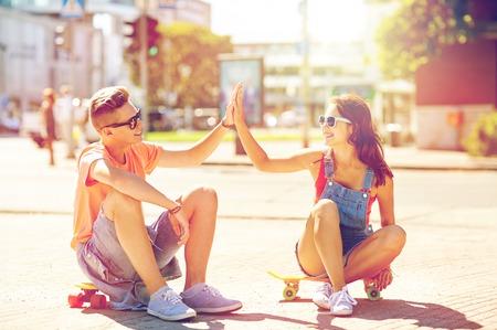 teenage couple with skateboards on city street 版權商用圖片 - 81768008