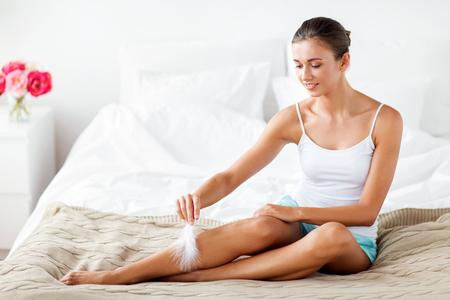 Vrouw met veer aan het raken van blote benen op bed Stockfoto - 81770207
