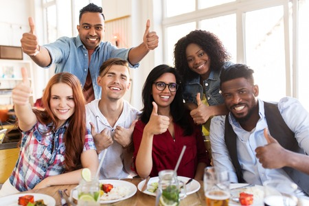 happy friends showing thumbs up at restaurant Stock Photo - 81770216