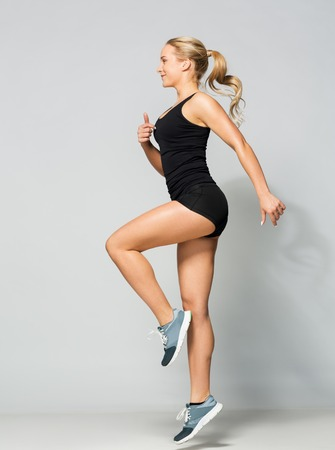 young woman in black sportswear jumping