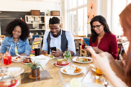 happy friends with smartphones at restaurant