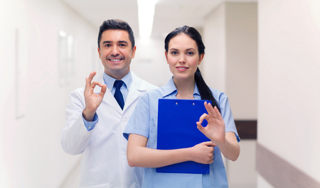 alright: healthcare, profession, people and medicine concept - smiling doctor and nurse with clipboard showing ok hand sign at hospital