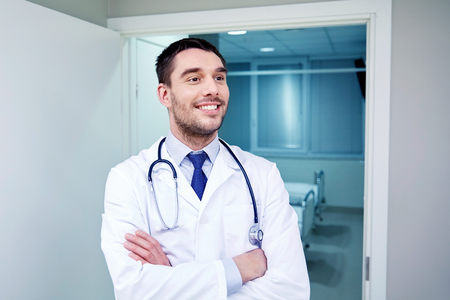 clinic, profession, people, health care and medicine concept - smiling doctor with stethoscope at hospital corridor